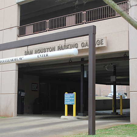 """Entrance to a parking garage with poles and clearance signs and reading """"Sam Houston Parking Garage"""" on top"""