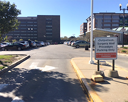 Hospital surface parking lot filled with cars and a barrier gate