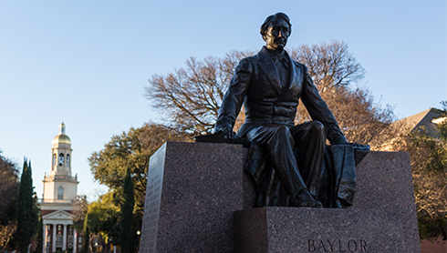Statue at Baylor University with school building in the back