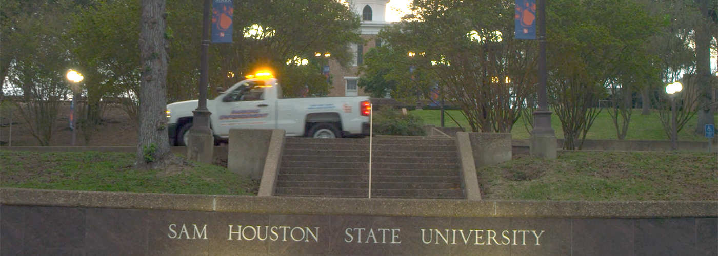 White enforcement truck passes front sign of Sam Houston State University