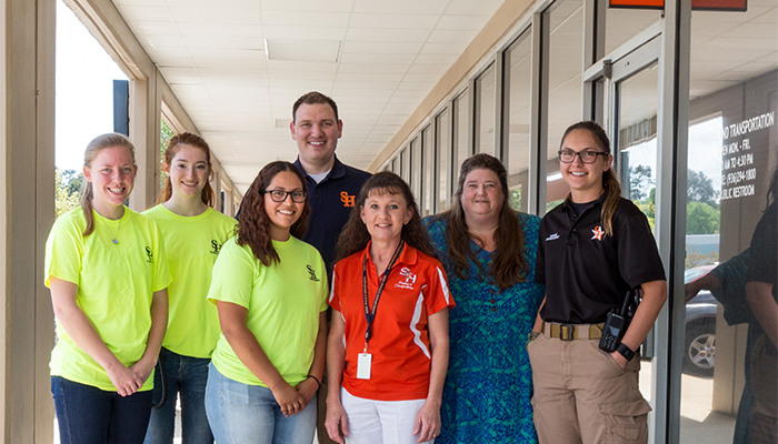 row of 7 parking staff members from SHSU smiling outside their parking office